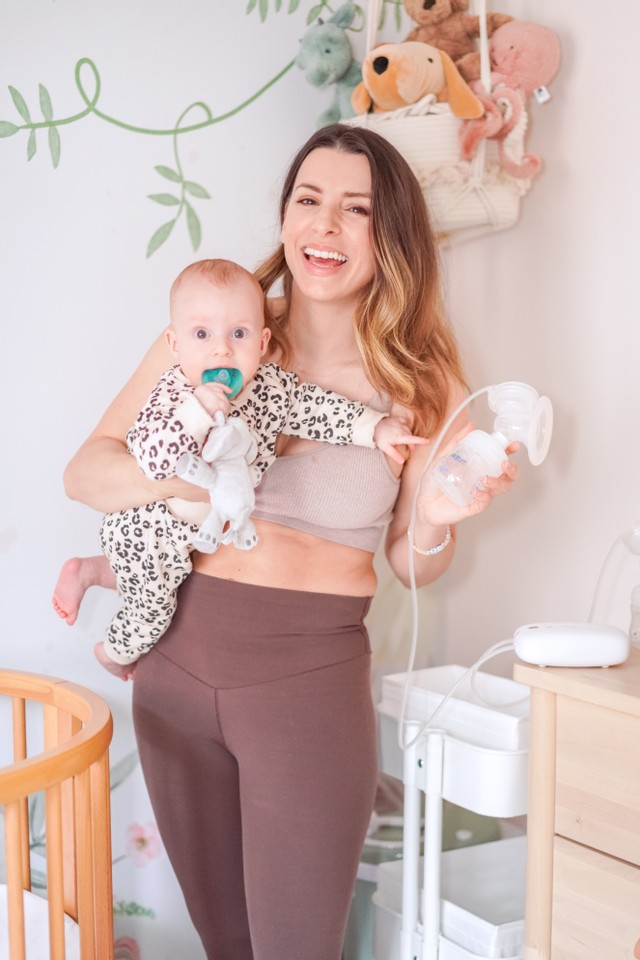 woman holding her baby and a breast pump