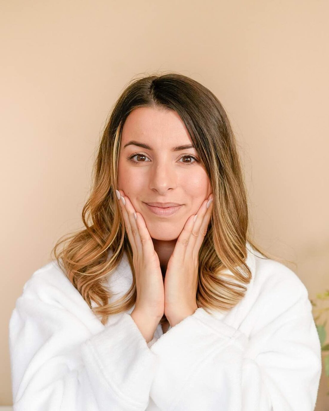 woman wearing a white dressing gown pressing her hands to her face