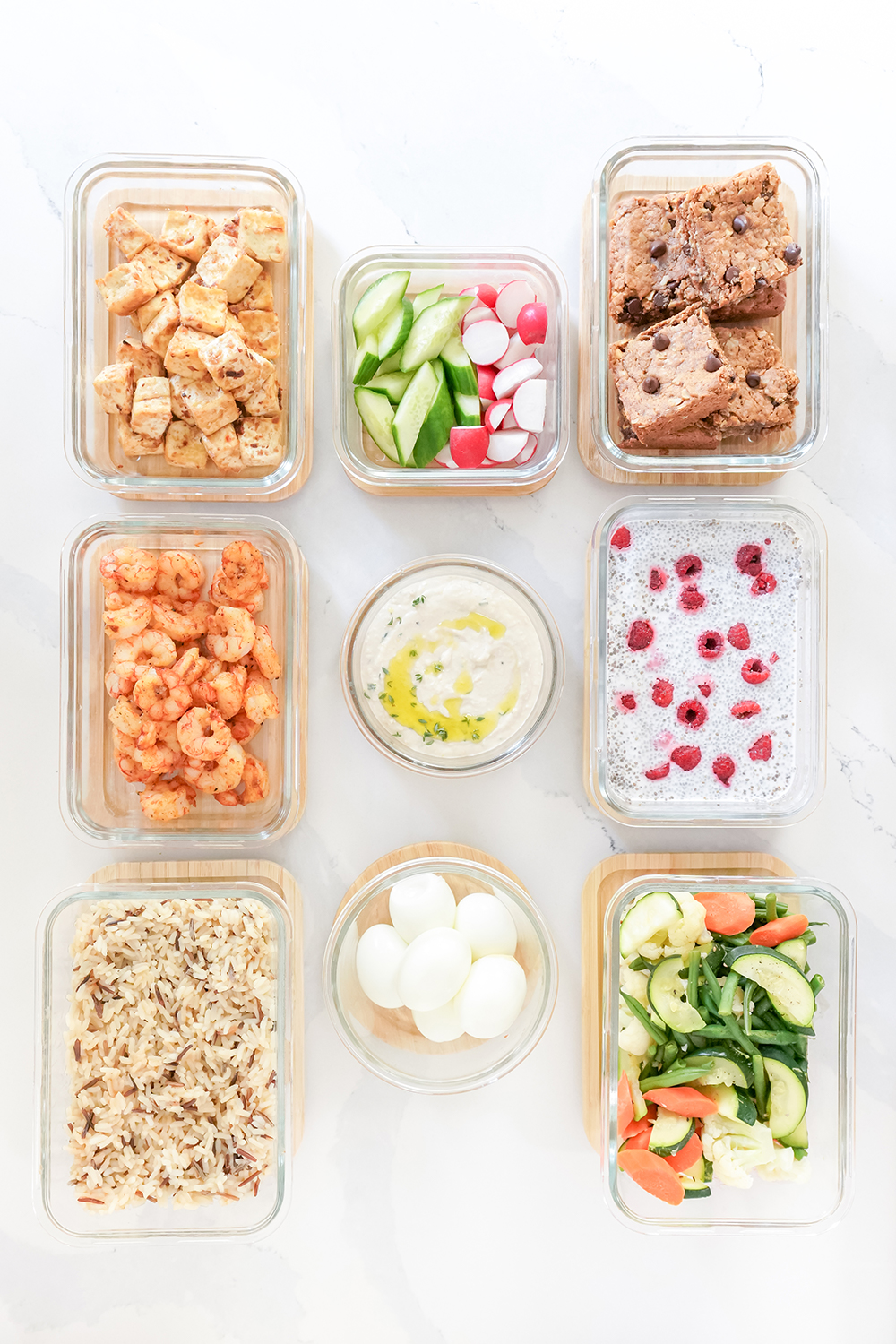 glass containers with a variety of meal prepped food inside them
