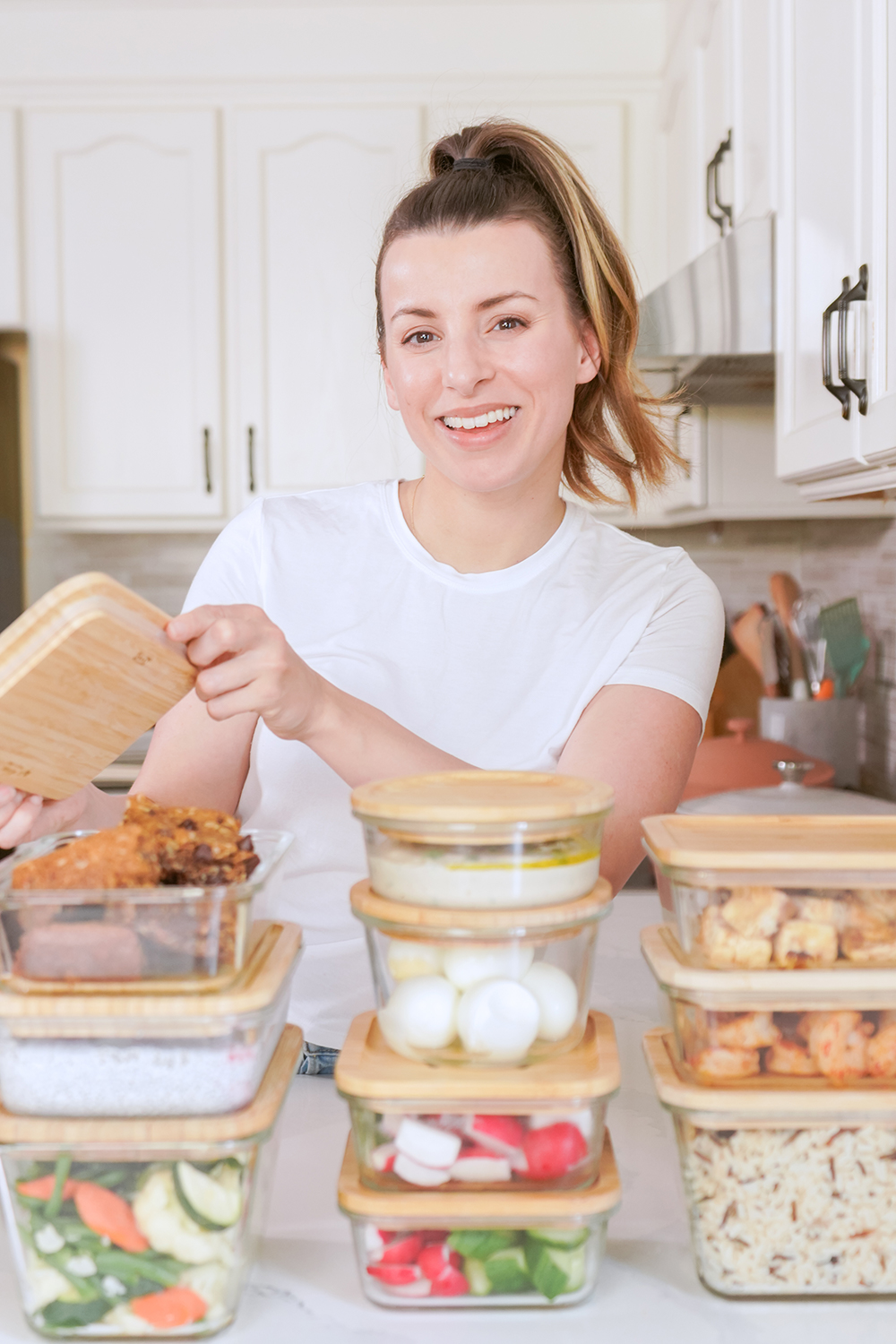 woman showing off meal prep equipment in her kitchen
