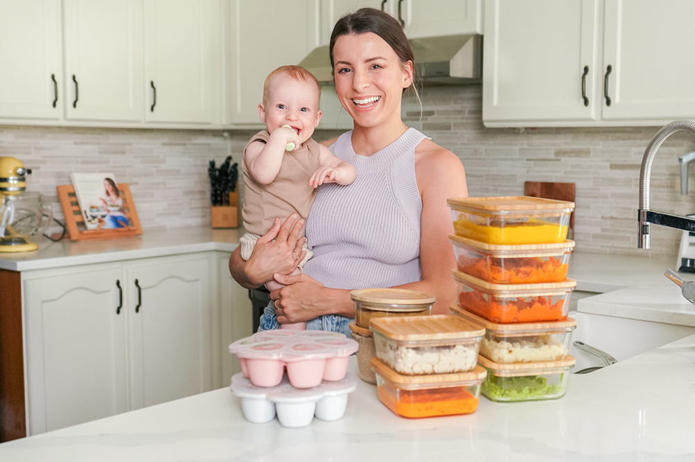 mother holding her baby in front of meal prepped baby food