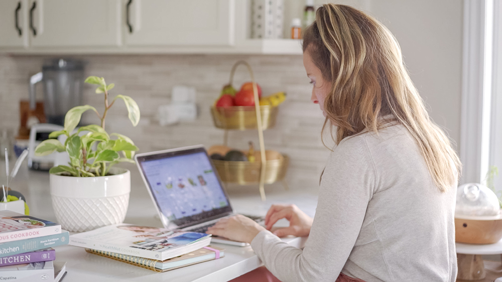 woman sitting in the kitchen doing work on a laptop