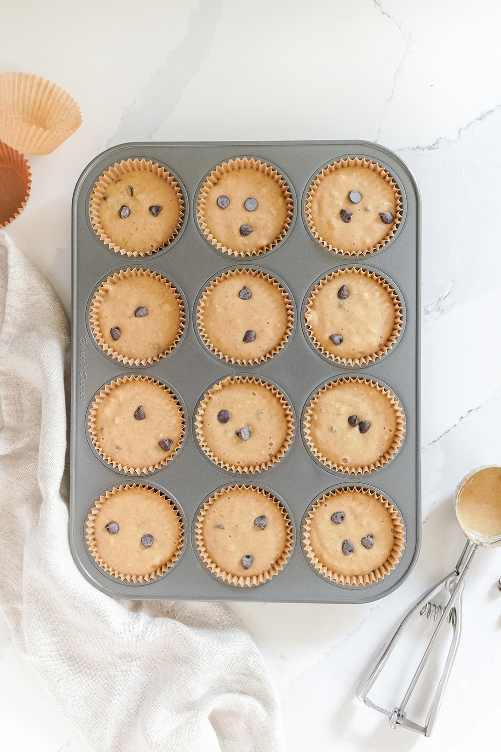 Uncooked Peanut Butter Banana Chocolate Chip Muffins in a baking tray