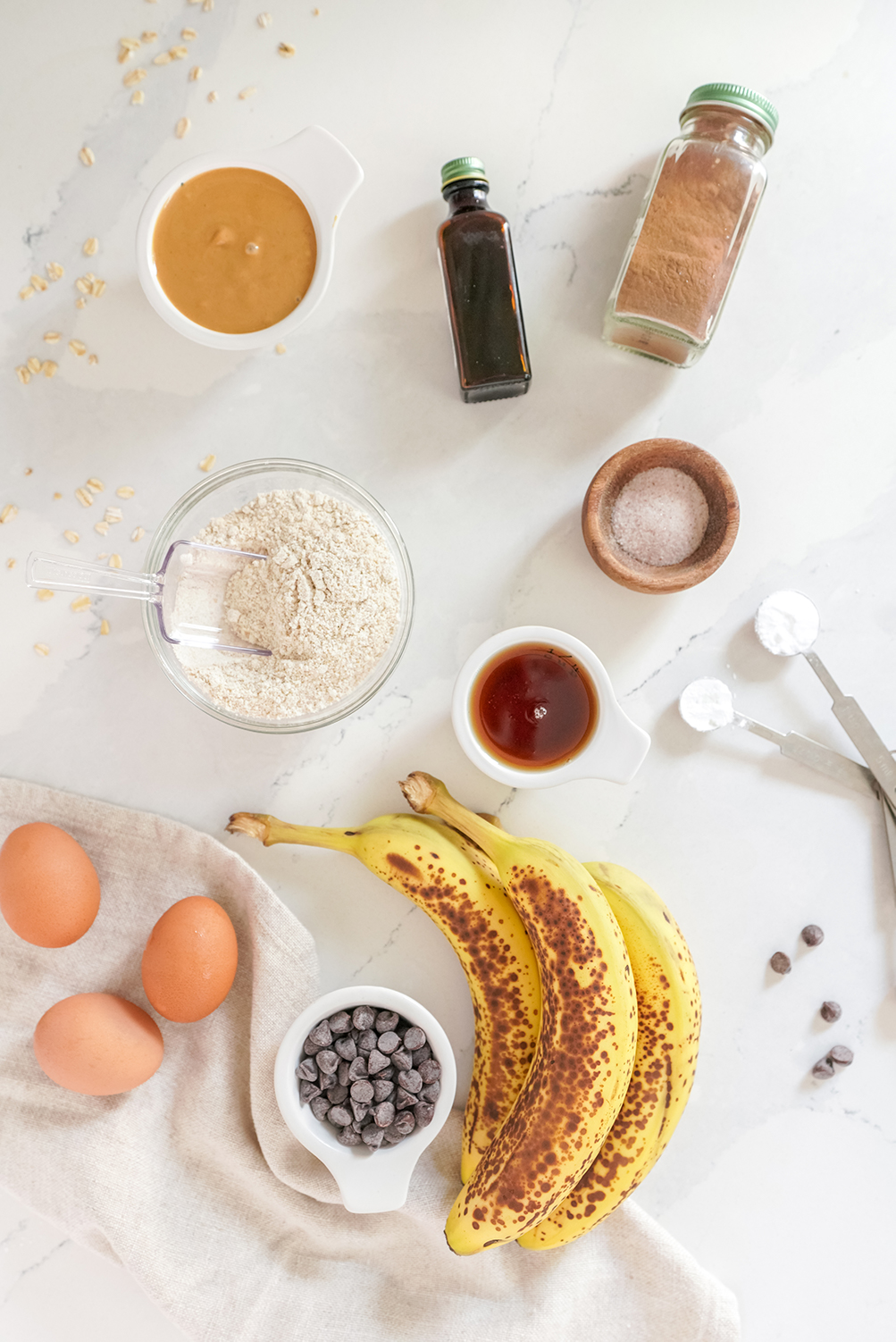 Bananas, flour, eggs and other ingredients on a white surface