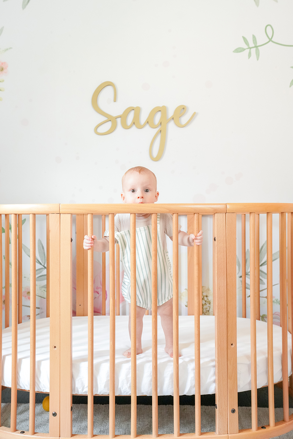 a 9 month old baby stood in her crib